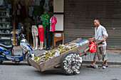 A man with a cart selling grapes in the former Jewish neighborhood in the Tilanqiao Historic Area of Hongkou district of Shanghai, China.