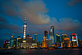 View from the Bund at night of the Huangpu River, the 492 meter high World Financial Center and the Oriental Pearl Television Tower in Pudong, Shanghai, China.