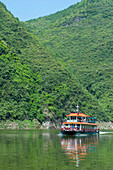 A tour boat near Badong on the Shennong stream, a tributary of the Yangtze River at the Wu Gorge (Three Gorges) in China.