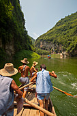 Chinese men rowing a traditional Sampan boat near Badong on the Shennong stream, a tributary of the Yangtze River at the Wu Gorge (Three Gorges) in China.
