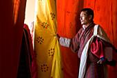 Man looking through curtains at performance, Festival, Trashichhoe Dzong (monastery), Thimpu, Bhutan