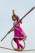 Girl performing tight rope act on the beach, Pondicherry, Tamil Nadu, India