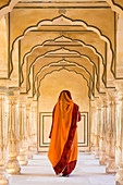 Indian woman walking along passageway, Amber Fort, Jaipur, Rajasthan, India. Model released.