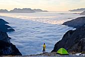 Man & tent above clouds, Italy, Italia\nTrentino-Alto Adige, South Tyrol\nBolzano district\nAlta Pusteria, Hochpustertal\nDolomiti di Sesto Natural Park