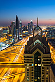 Elevated view over the modern Skyscrapers at dusk, along Sheikh Zayed Road looking towards the Burj Kalifa, Dubai, United Arab Emirates