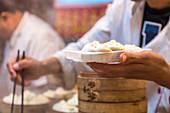 Person holding steamed dumplings at Donghuamen Night Market, Wangfujing, Beijing, China