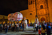Women dressed in a regional costume and giant puppets dressed as a bride and groom during a Calenda, a procession on the Plaza Santo Domingo, celebrating a wedding in the city of Oaxaca de Juarez, Oaxaca, Mexico.