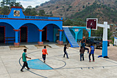 Local people playing basketball on the zocalo (main square) in the Mixtec village of San Juan Contreras near Oaxaca, Mexico.