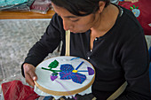 A Mexican woman is doing embroidery in a sewing and how to establish a handicraft business workshop, which is taught by US women in the Mixtec village of San Juan Contreras near Oaxaca, Mexico.