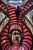 Curved wooden staircase in library, Livraria Lello & Irmão bookstore, Porto, Portugal, Europe