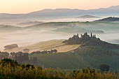 Sunrise, villa on a hill in Val d'Orcia, Tuscany, central Italy
