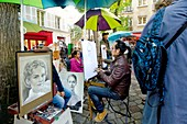 Montmartre - Place du Tertre - artist painting a tourist's portrait / caricature. Paris, France.