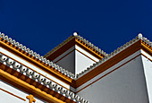 White house with colored accents in the Moorish style against an azure blue sky, near Pilas, Andalusia, Spain