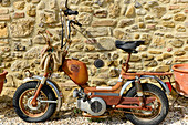 Old, rusty scooter on a stone house wall, Rustic campsite, Perugia, Italy