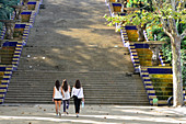 Three young women are walking in the park towards a staircase, Montjuic, Barcelona, Catalonia, Spain