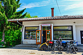 Travel bikes and female cyclist in front of a tiny shop, Perjasica, Croatia