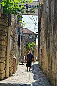 A very old woman is walking on a stick through the narrow streets, Pakostane, Croatia