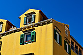 Old, yellow house against a blue sky in Sibenik, Adriatic Sea, Dalmatia, Croatia