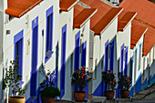 Row of houses on a steep street with blue windows and red roofs, Odeceixe, Algarve, Portugal