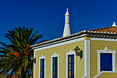 Typical, colorful house with palm tree in the Algarve, Luz, Portugal