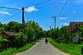 Woman cyclist on a quiet street in a small village, Kerkafalva, Hungary