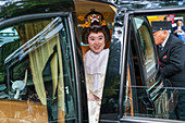 Woman in traditional wedding dress in chauffeur driven car, Tokyo, Japan