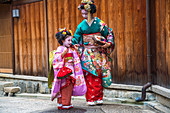 Mother and young daughter dressed in traditional geisha Japanese dress, Kyoto, Japan