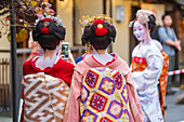 Women in traditional Geisha dress taking photos with a smartphone in Kyoto, Japan