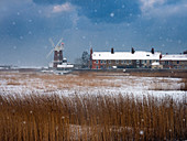 Cley Mill and reedbed in winter snow storm Norfolk