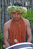 Cook Islander man plays music on a large drum instrument in Rarotonga, Cook Islands. Real people. Copy space