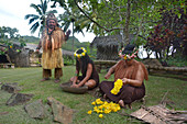 RAROTONGA - JAN 16 2018:Cook Islander tribal chief stands beside two Cook Islander women works outdoor in a Maori village in the highlands of Rarotonga, Cook Islands