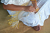 Young attractive and exotic Polynesian Cook Islander woman weaving a hand fan in Rarotonga, Cook Islands. Real people. Copy space