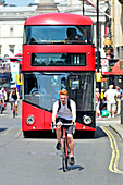 Young man cycling without a helmet in Whitehall in front of a red double decker bus, London, England, UK.