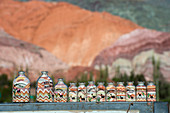 Souvenir bottles with colorful sand from the rock formations of Cerro de los Siete Colores, (Seven Colors Hill) in the Andes Mountains in Purmamarca, Jujuy Province, Argentina.