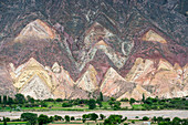 View of colorful rock formations and erosion near Tilcara in the valley of Quebrada de Humahuaca, Andes Mountains, Jujuy Province, Argentina.
