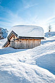 landscape of snow-covered mountain huts in the locality Ciamp de Lobia, Fedaia pass, Rocca Pietore, Marmolada, Dolomites, Belluno, Veneto, Italy