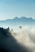Gardena Pass, Dolomites, Bolzano district, South Tyrol, Italy, Europe. Fog drifts around some crags, in the background the mountains of Tofana di Mezzo and Tofana di Dentro