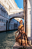 Typical mask of Carnival of Venice with the Bridge of Sighs in the background, Venice, Veneto, Italy