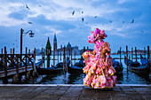 Typical mask of Carnival of Venice in Riva degli Schiavoni with St. George's island in the background, Venice, Veneto, Italy