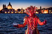 Typical mask of Carnival of Venice with Church of La Salute in the background, Venice, Veneto, Italy
