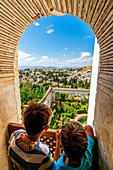 Two children look at Patio de la Sultana (Court of the Sultana's Cypress Tree) from mirador on top of Generalife Palace, Granada, Andalusia, Spain