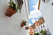 Hanging flowerpots on buildings with Maria De La Mesa Church (Iglesia de Santa Maria de la Mesa) in the background, Zahara de la Sierra, Cadiz province, Andalusia, Spain