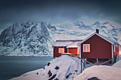 Red fisherman's cabins covered with snow, Hamnoy, Nordland, Lofoten Islands, Norway