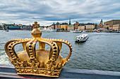 Gilded Crown on Skeppsholmsbron (Skeppsholm Bridge) with Gamla Stan old town in background, Stockholm, Sweden
