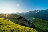 Stone hut in green pastures lit by warm sunburst at dawn, Tombal, Soglio, Val Bregaglia, canton of Graubunden, Switzerland