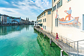 Woman on elevated walkway on Limmat River beside the painted buildings of Lindenhof, Zurich, Switzerland