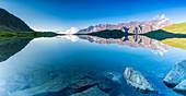 Panoramic of Cima di Pietra Rossa mirrored in clear water of Lago Nero at sunrise, Gavia Pass, Valfurva, Valtellina, Lombardy, Italy