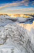 Sunrise over the winding road of Stelvio Pass covered with snow in autumn, aerial view, Bolzano province, South Tyrol side, Italy