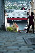 Rear view of man photographing the Hurtigruten cruise ship with smartphone, Bergen, Hordaland County, Norway