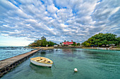 Dramatic sky over Notre Dame Auxiliatrice Church seen from pier in the turquoise sea, Cap Malheureux, Indian Ocean, Mauritius